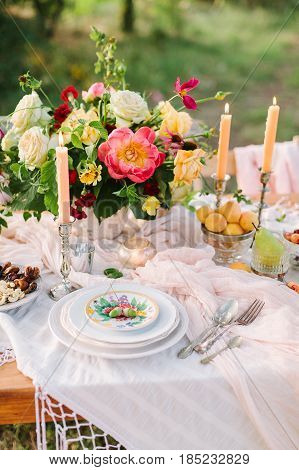 picnic, food, summer, holiday concept - close-up on part of the festively decorated table with a beautiful bouquet of roses and peonies, candles in candlesticks, apricots, cherries, pear, glassware