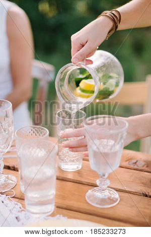 picnic, people, summer, holiday concept - female hands pouring lemonade from the decanter into a glass beaker, a jug with slices of lemon, lime, mint leaves, water, decorated table, selective focus
