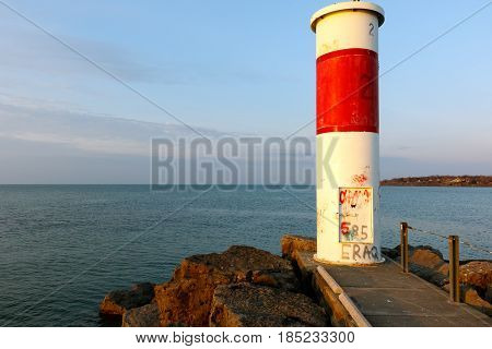red and white lighthouse on Lake Ontario shore, near Rochester, New York