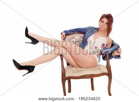 A beautiful slim young woman in a baby doll night gown sitting in an old armchair with her legs over the side isolated for white background.