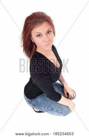 A beautiful young Caucasian woman crouching on the floor looking up in jeans and blouse isolated for white background.