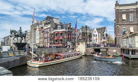 AMSTERDAM , NETHERLANDS - APRIL 31, 2017 : People enjoying the sightseeing boat tour in the canals of Amsterdam, Netherlands