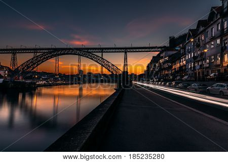 Long exposure of the iconic Dom Luis I bridge at sunset  designed by Gustav Eiffel crossing the Douro River,historical Ribeira and Se District in Porto,Portugal.Unesco World Heritage Site