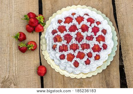 cake with fresh strawberries on wooden table (top view)