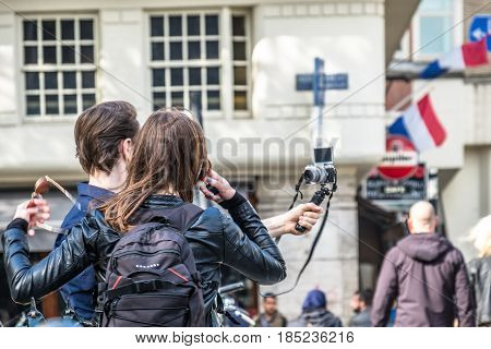 AMSTERDAM , NETHERLANDS - APRIL 31, 2017 : Couple taking selfies while people walking around in Amsterdam