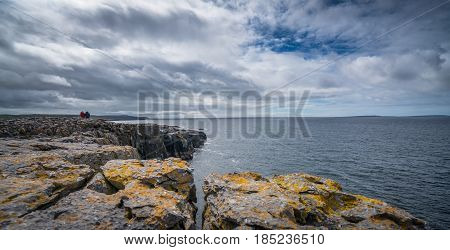 Two unidentified people sitting on the cliffs edge in Doolins Bay, The Burren, County Clare, Ireland
