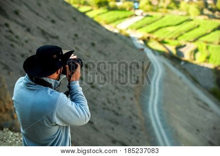 Man photographing fields in mountains of Nepal. Kingdom of Mustang. Himalayas.