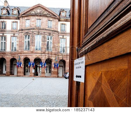 STRASBOURG FRANCE - MAY 7 2017: French polling station Bureau de vote sign on door with French flags ready for second round of the French presidential election to choose between Emmanuel Macron and Marine Le Pen
