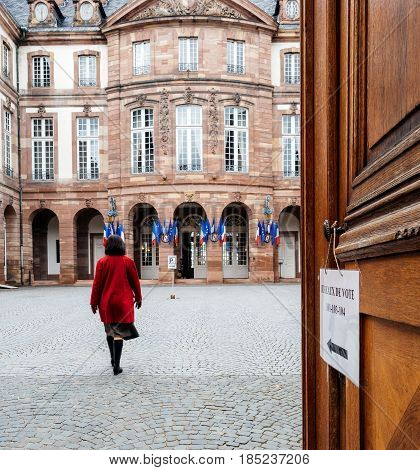 STRASBOURG FRANCE - MAY 7 2017: Woman in read coat heading to polling station Bureau de vote during the second round of the French presidential election to choose between Emmanuel Macron and Marine Le Pen