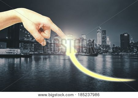 Hand pointing at creative upward arrow on night city background. Growth concept
