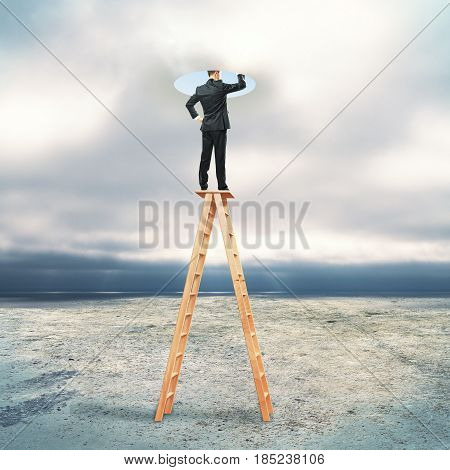 Businessman on abstract ladder looking into bright hole. Dull sky background. Creativity concept