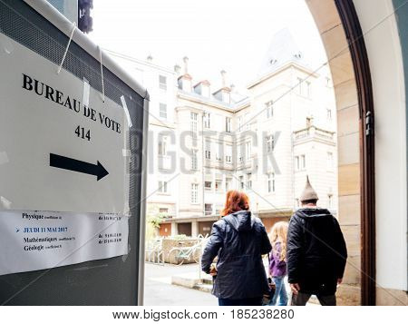 STRASBOURG FRANCE - MAY 7 2017: Bureau de vote sign in French city with family going to polling place during the second round of the French presidential election to choose between Emmanuel Macron and Marine Le Pen