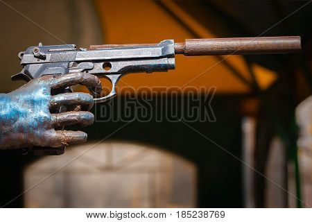 The hand holds the gun. Pistol with a silencer.