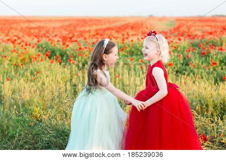 girl model, childhood, fashion concept - the happiness of two little girls, one of the beauties in a blue dress, the second a blond in a red dress, they stand and hold hands over field of poppies