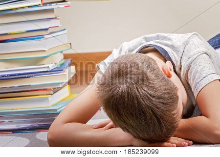 Tired boy lying near big stack of books.