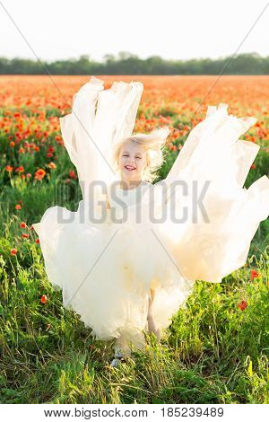 girl model, poppies, fashion, summer nature concept - laughing elegant girl with white hair playing in a field of poppies with her white wedding dress, the hem of the dress billowed above her head