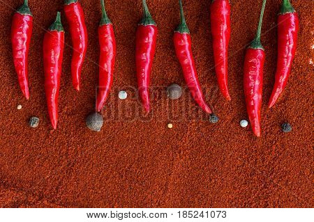 red hot chili peppers, popular spices concept - decorative pattern of chili pods on a brown background from a powder of red indian curry, flat lay, free space for text