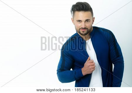 fashion. Handsome bearded man young athletic model sexy macho with stylish hair in fashionable blue sportswear posing on white background. Sport fashion or healthy lifestyle copy space