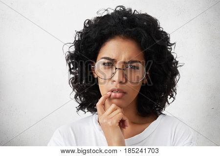 Serious Attractive Young Dark-skinned European Woman Wearing White Casual T-shirt And Round Glasses