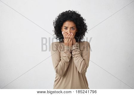 Close Up Portrait Of Upset Scared Black Woman, Covering Her Mouth With Both Palms To Prevent Screami