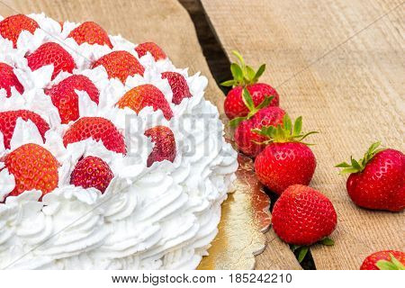 strawberry and cream cake (half cake on wooden table)
