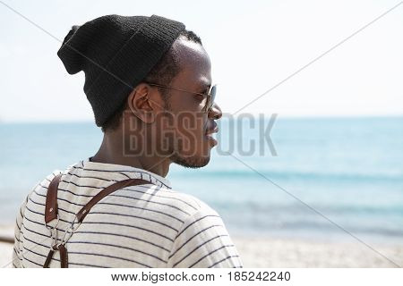 Portrait From Behind Of Happy African American Traveler Standing On Beach With Backpack On His Shoul
