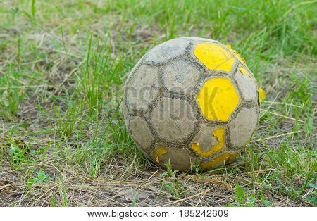 Old football (soccer ball) on an old neglected field.