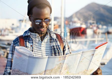 Outdoor Shot Of Cheerful And Stylish Young Dark-skinned European Male Traveler With Knapsack Studyin