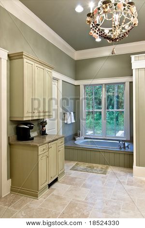 spacious bathroom with custom cabinets and large window