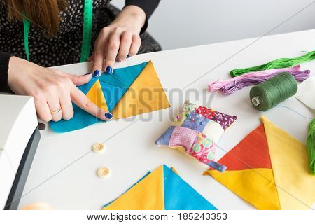 needlework and quilting in the workshop of a young woman, a tailor - close-up on hands of a tailor with scraps of colorful fabrics lying on a white table buttons, pins, pin cushion