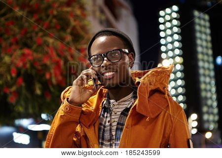 Outdoor Evening Shot Of Handsome Afro American Traveler Dressed In Winter Coat And Headwear Using Mo
