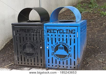 Asheville, North Carolina, USA - April 22, 2017: Close up of black and blue public landfill and recycling bins on a downtown street