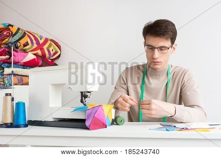 quilting and patchwork - handsome male in glasses with a tape measure around his neck sitting on desk with a sewing machine, he threads the needle, near laid patchwork and spools of thread