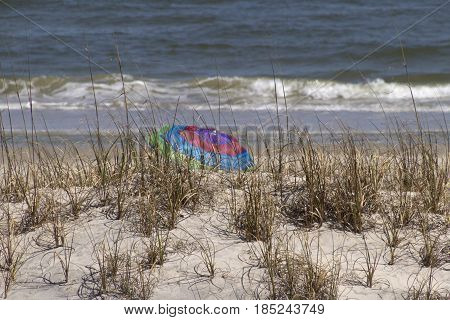 A colorfully striped beach umbrella is tucked away and hidden behind a sand dune by the sea on a sunny day