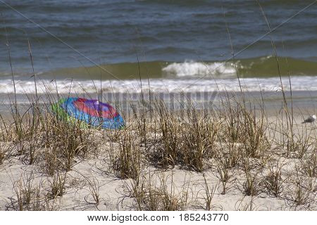 A colorful beach umbrella is tucked away and hidden behind a sand dune by the sea on a sunny day