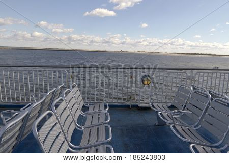 Ferry deck with chairs i sight of land as it crosses the ChesapeakeBay on a sunny day