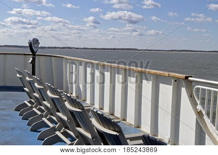 Ferry observation deck with chairs and a pay per view telescope as it nears land while crossing the Chesapeake Bay on a sunny day