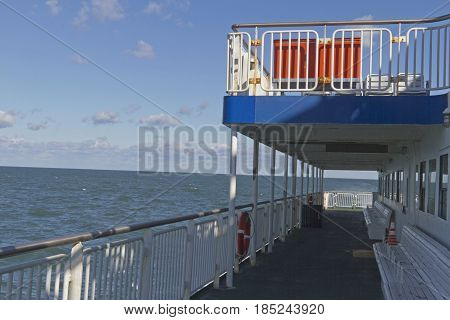 Two layers decks on a ferry with benches fencing and life preserver as it crosses the ChesapeakeBay on a sunny day