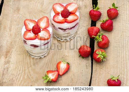 Dessert (trifle) with cream and fresh strawberries on wooden table