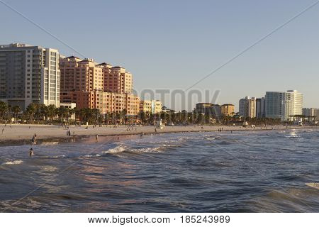 Clearwater, Florida - January 24, 2017: Late afternoon at Clear water Beach as seen from the water looking at people enjoying the beach and water and the colorful buildings that line the shore reflecting on the incoming waves
