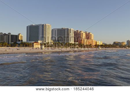 Clearwater, Florida, USA - January 24, 2017: Late afternoon at Clear water Beach as seen from the water looking at people enjoying the beach and water and the colorful buildings that line the shore reflecting on the incoming waves