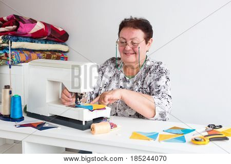 patchwork and quilting in the workshop of a tailor woman on white background - elderly woman with glasses sews on the sewing machine scraps of colorful fabric for patchwork