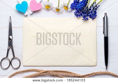 Letter hearts pen scissors and delicate flowers on white natural wooden background. Classic letter corespondence abstract concept.