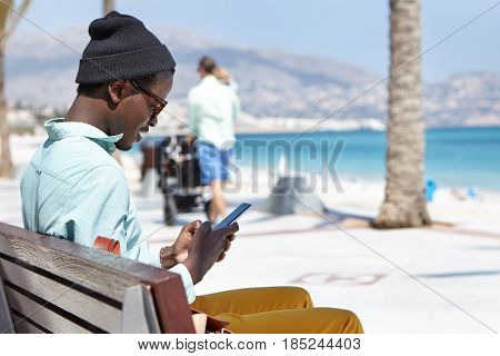 Side View Of Young Afro American Male Hipster Dressed In Stylish Clothing Typing Text Message Via Sm