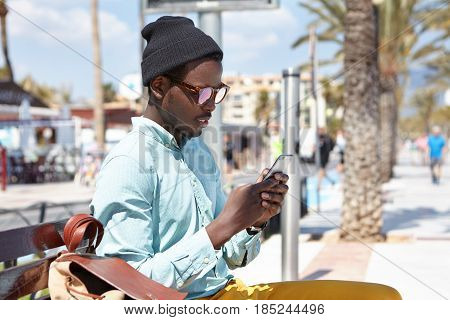 Always In Touch. Fashionable Black European Tourist Sitting On Bench With Backpack Using Free City W