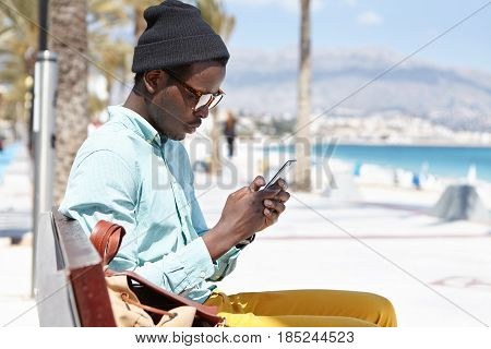 Staying Connected. Attractive Young African Man Sitting On Bench Along Promenade At Seaside, Surfing