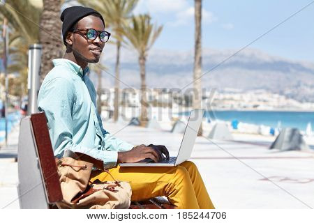 Relaxed Fashionable Dark-skinned Student Waiting For Friends For Walk, Sitting On Bench At Seaside,