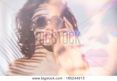 Summer style portrait of young attractive woman wearing sunglasses. Face close up. Tropical holiday fashion beauty concept