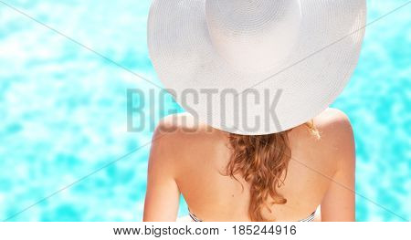 Woman wearing hat on the tropical beach. Summer holiday fashion concept