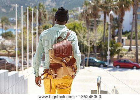 Rear View Of Unrecognizable African Male Student Carrying Leather Knapsack On His Shoulder Walking O